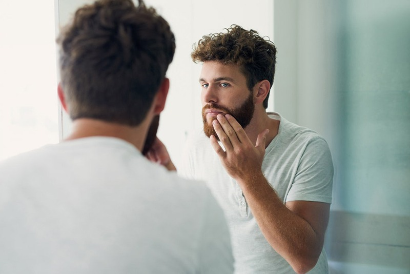 Man looking in mirror discovering benefits of using beard oil